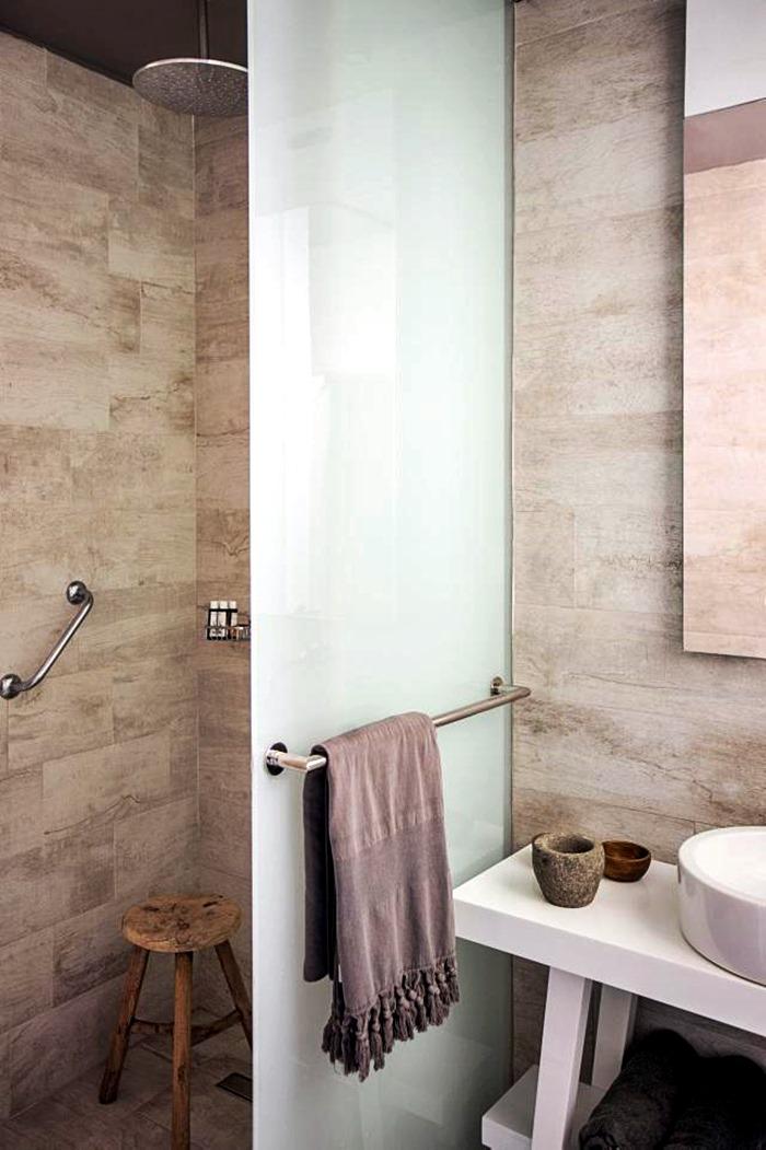 banheiro com barra de segurança e toalheiro na porta do box