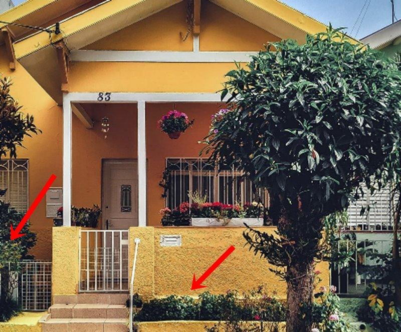 casa amarela com pequeno jardim e jardineira