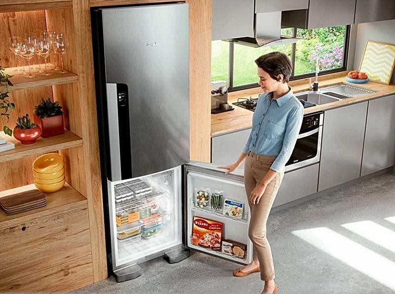 mulher na cozinha abrindo a porta do congelador da geladeira inverse