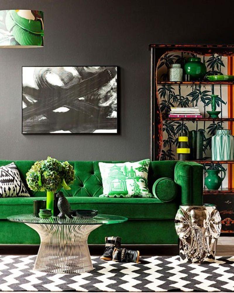 sala com parede preta e sofá verde de veludo