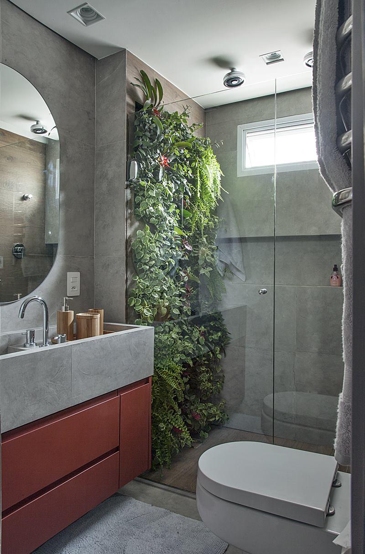 banheiro com espelho oval e parede com plantas no box