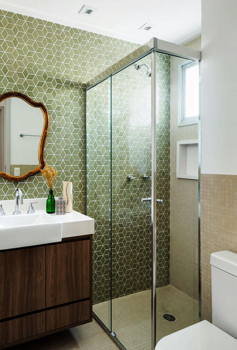 Banheiro verde com espelho emoldurado